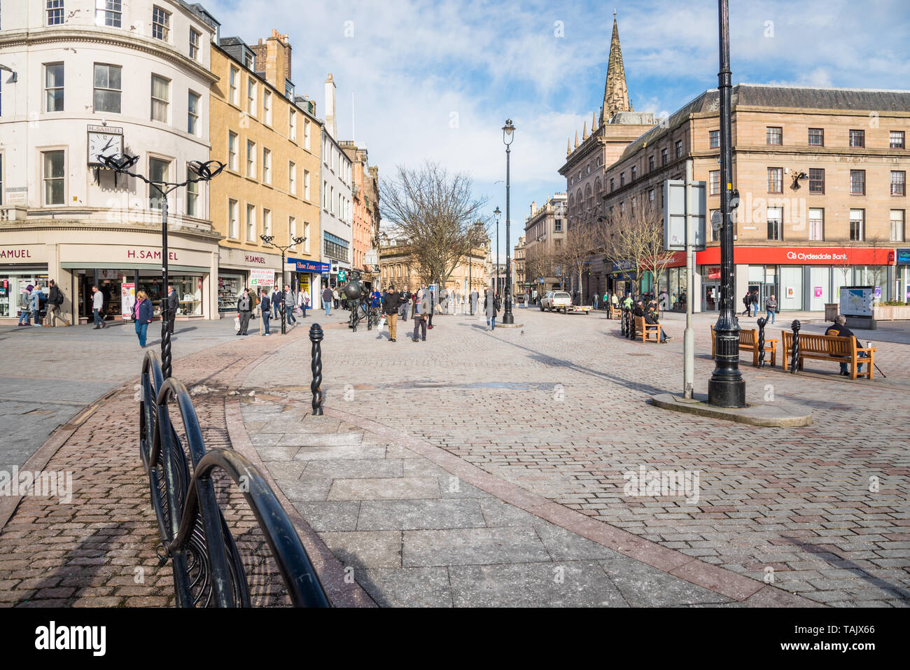 Dundee, UK - March 8, 2018: People strolling around the pedestrainized city centre lined with shops and restaurants on a sunny winter day - Stock Image