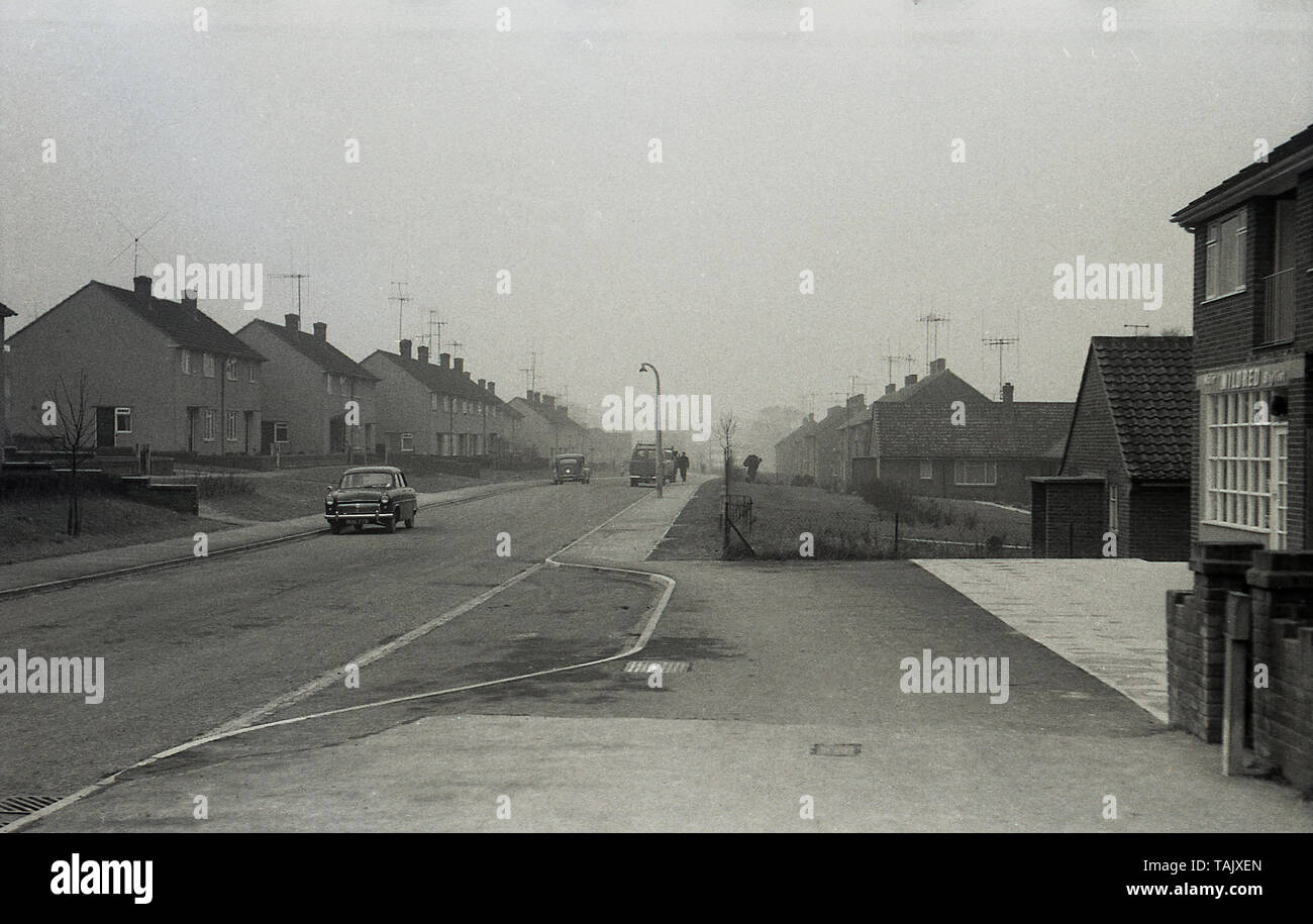 1955, historical, a post-war built housing estate, showing a local store and transport of the era parked in an empty treeless road. - Stock Image