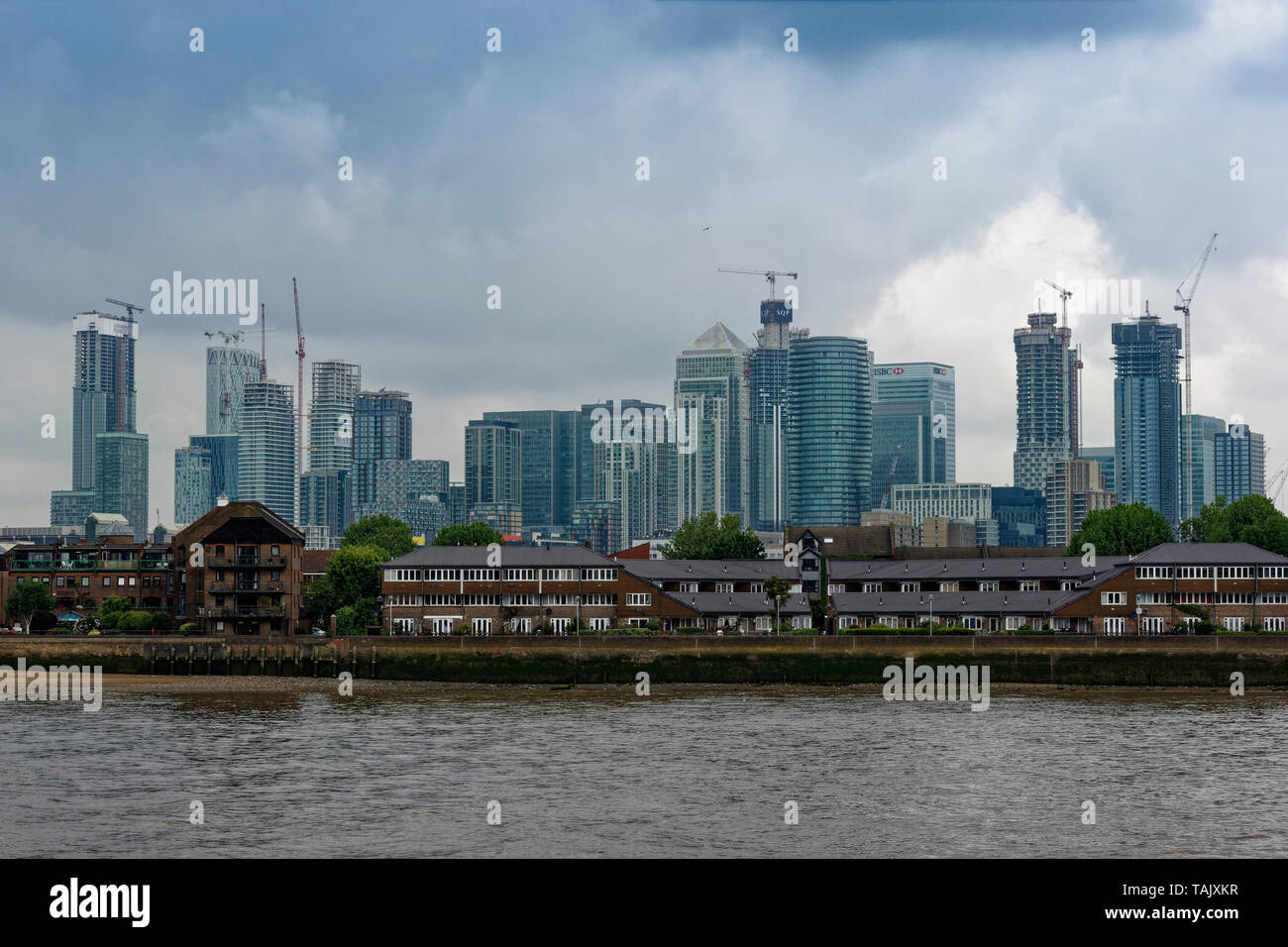 LONDON ISLE OF DOGS SKYSCRAPERS OF CANARY WHARF LOOM OVER THE RIVER THAMES - Stock Image