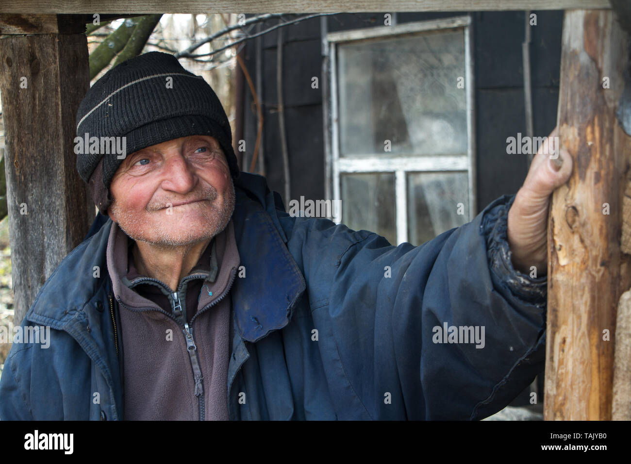 An old man in sloppy clothes stands on the threshold of his own ruined house and looks into the distance, loneliness in the village, life beyond pover Stock Photo