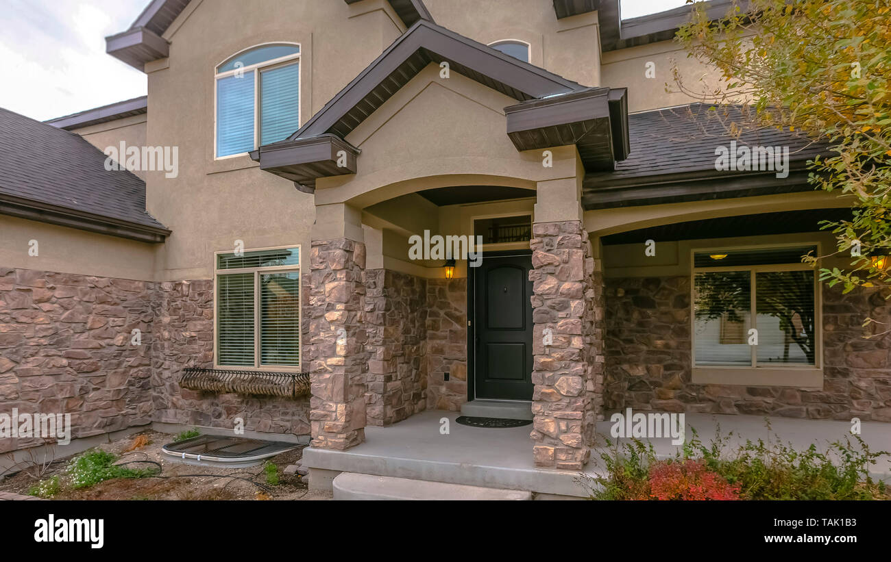 Facade of a home with stone wall and welcoming covered front