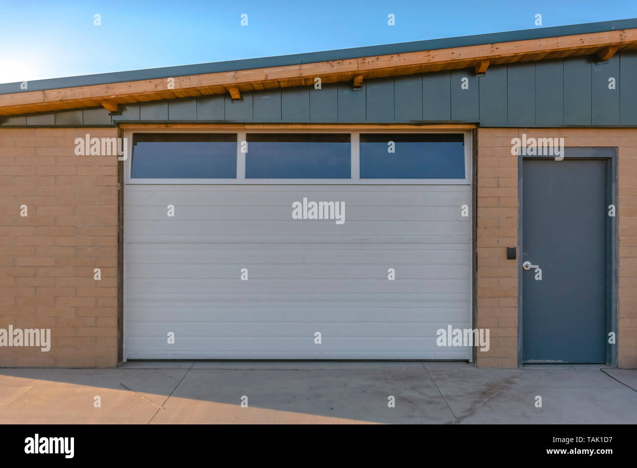 Exterior View Of A Building With Brick Wall Against Blue Sky On A Sunny Day The Building Has A Gray Door And White Garage Door With Small Windows Stock Photo Alamy