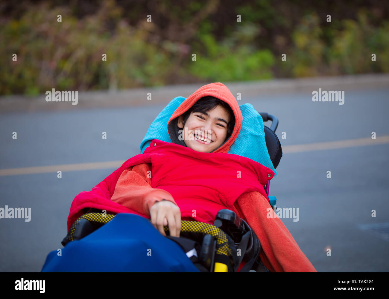 Smiling twelve year old special needs biracial boy in wheelchair outdoors on the road in cold weather wearing sweater and vest - Stock Image