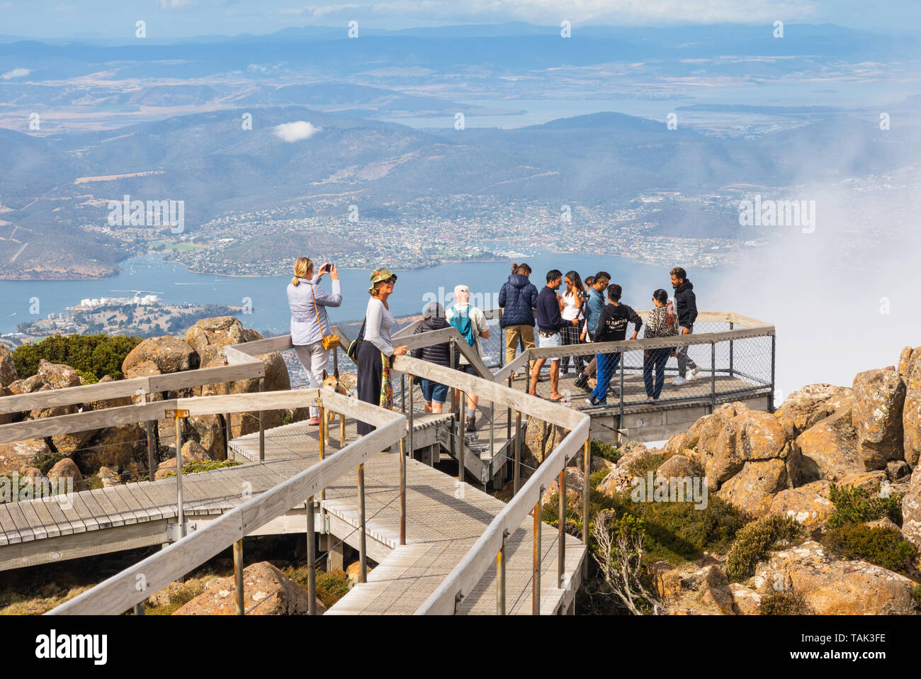 TASMANIA, AUSTRALIA - FEBRUARY 16, 2019: Tourists on a viewing platform on top of Mount Wellington, looking at Hobart, the capital city of Tasmania in Stock Photo