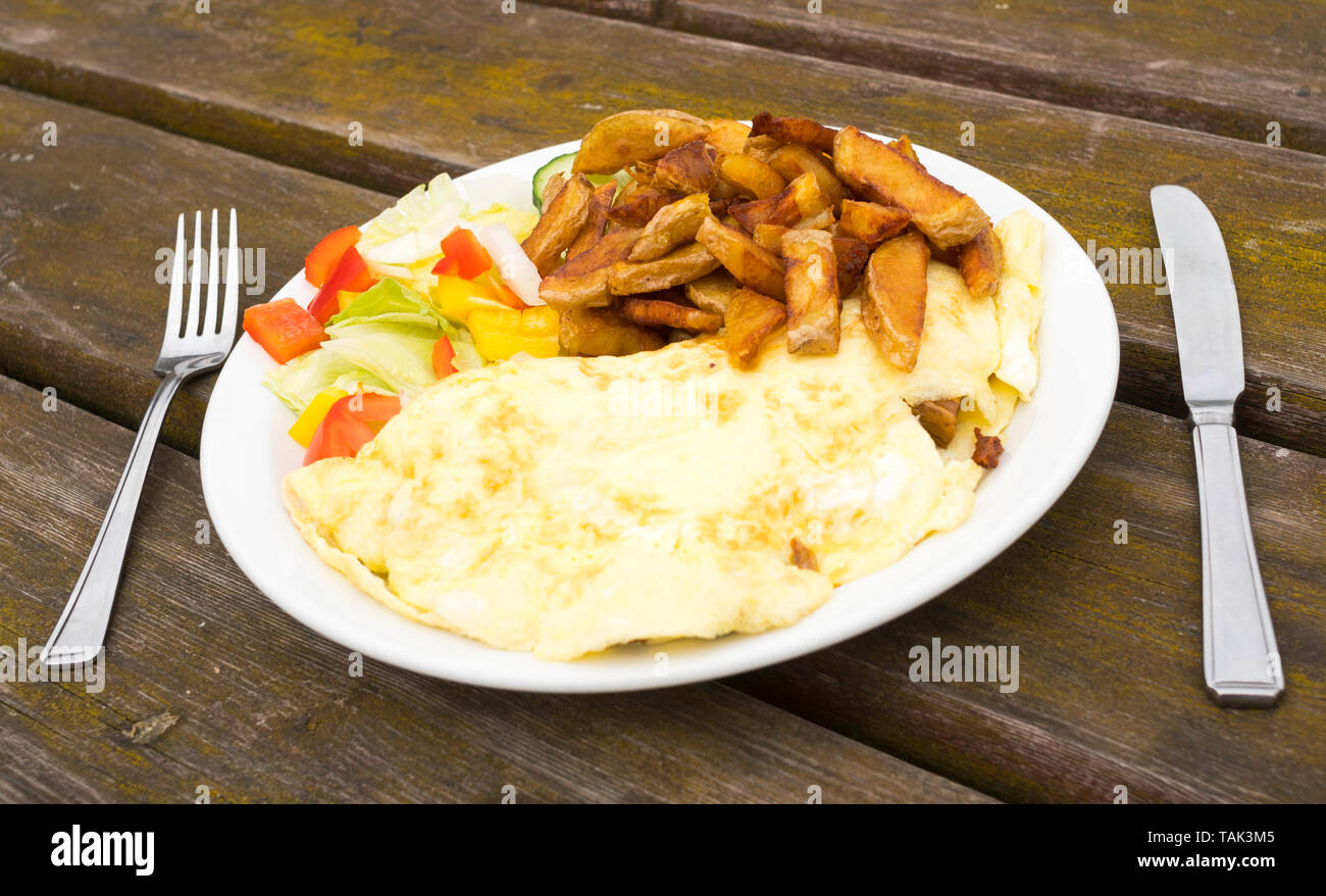 Plate of mushroom omelette, chips and salad with knife and fork on a wooden table, Hownsgill Tea Room, Consett, England, UK - Stock Image