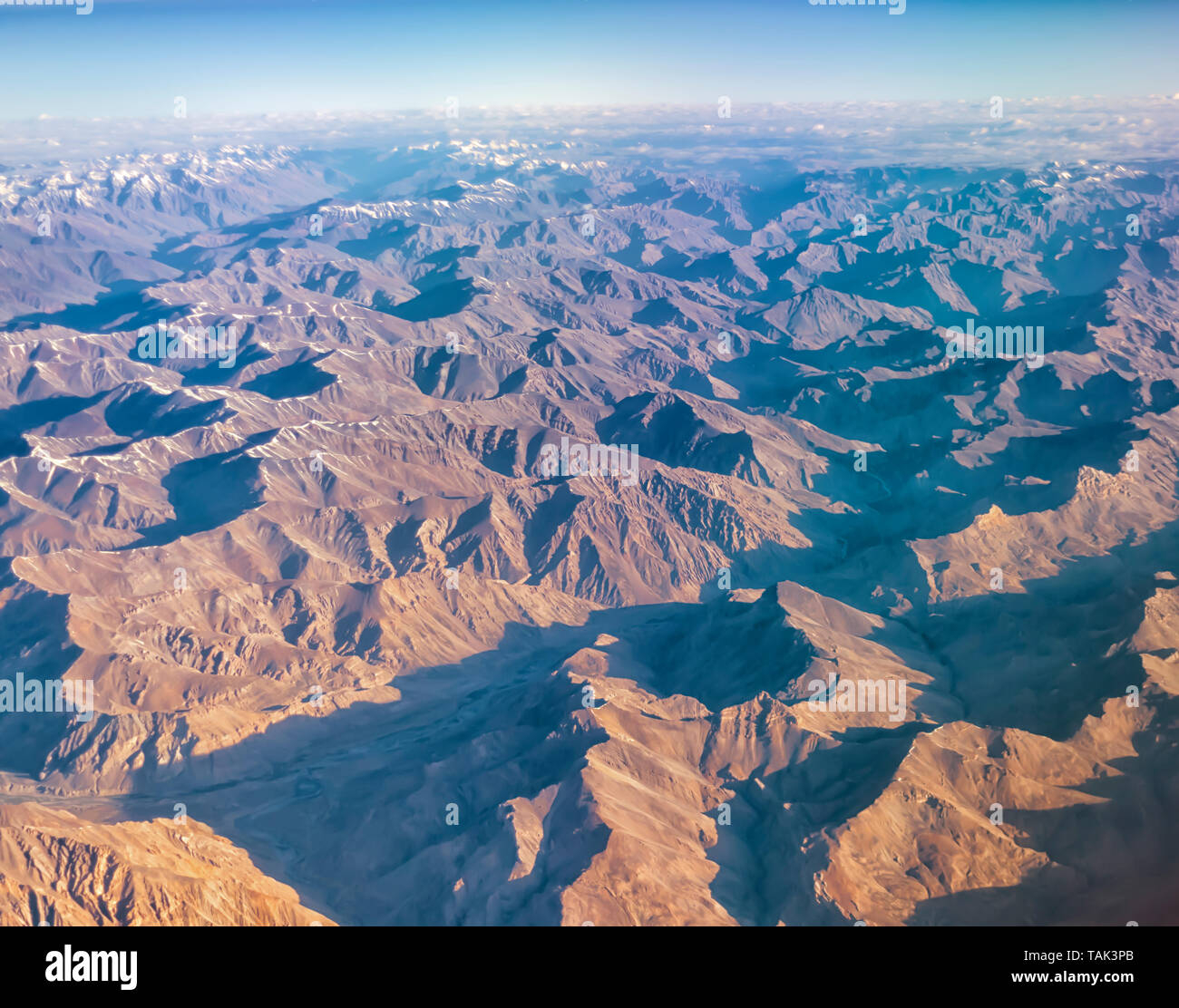 An aerial view of the barren mountains of the Zanskar range of inner Himalayas in India. Taken from a plane on an early July morning. - Stock Image