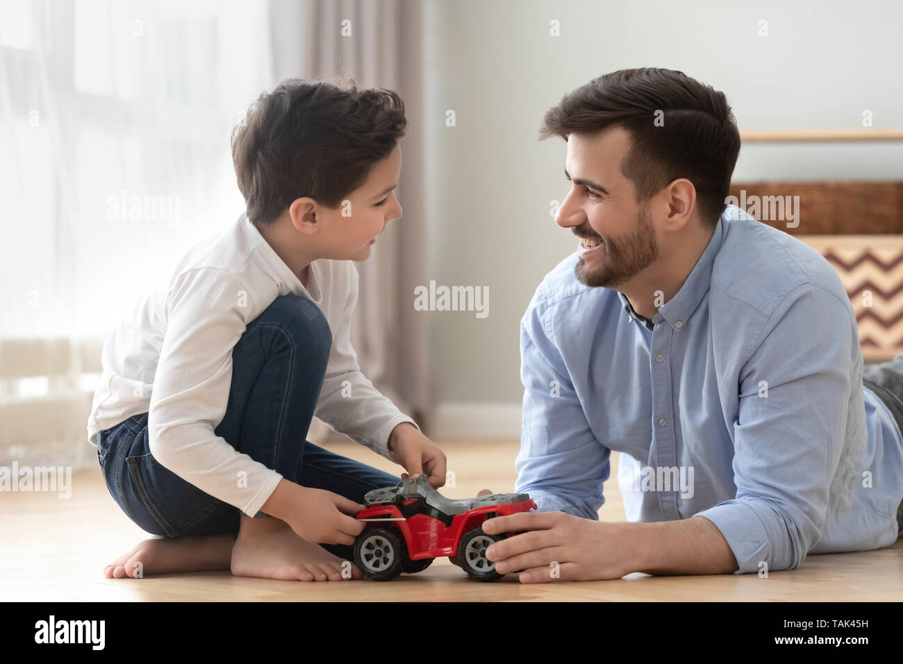 Happy father and son lying on floor have fun playing with toy car racing together, smiling dad and boy child relax at home engaged in game, laugh enjo Stock Photo