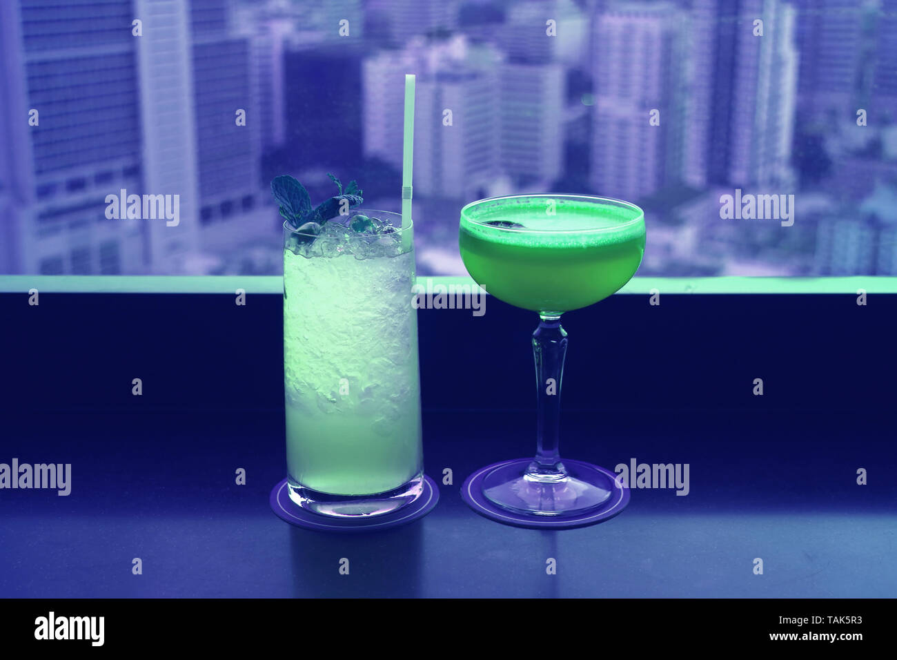 Two different type of cocktails in vibrant green color on the rooftop bar's table with blurry skyscrapers view in background - Stock Image