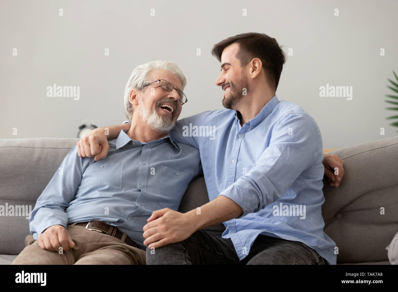 Happy Grown Son Sit On Couch Talk With Senior Dad Stock Photo