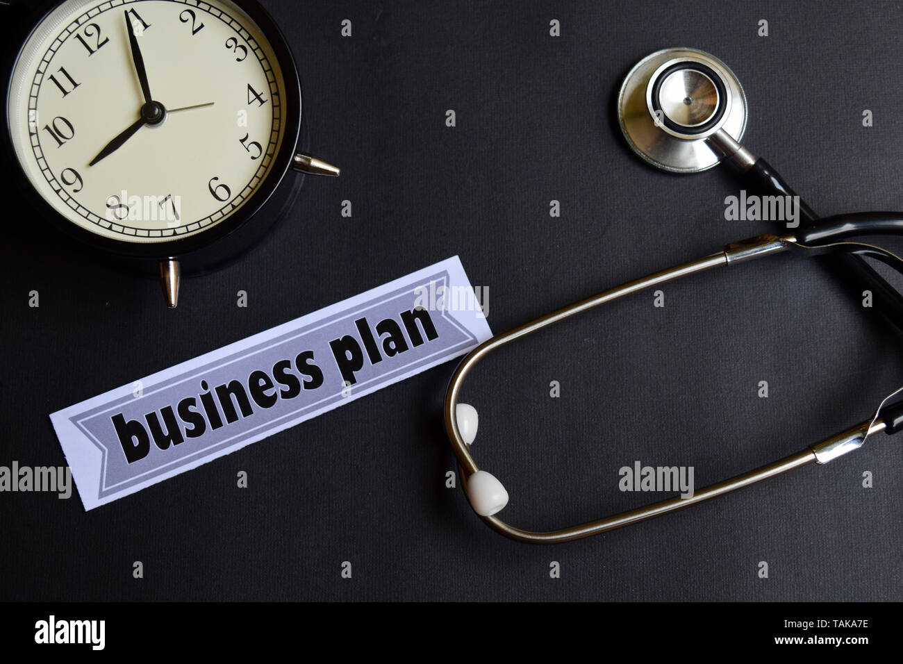 Business plan on the paper with Healthcare Concept Inspiration. alarm clock, Black stethoscope. - Stock Image