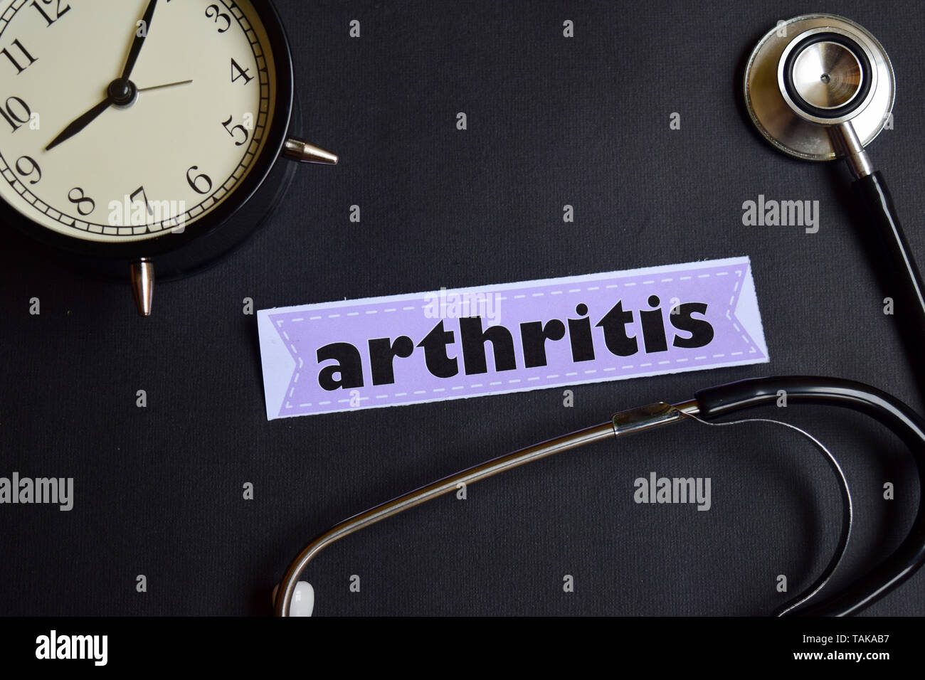 arthritis on the paper with Healthcare Concept Inspiration. alarm clock, Black stethoscope. - Stock Image
