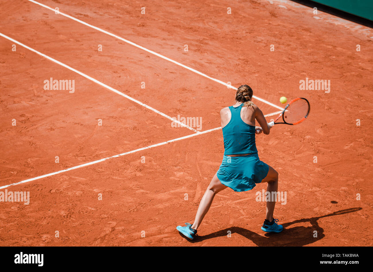 Back view  of a woman playing backhand in tennis outdoor competition game, running, professional - Stock Image