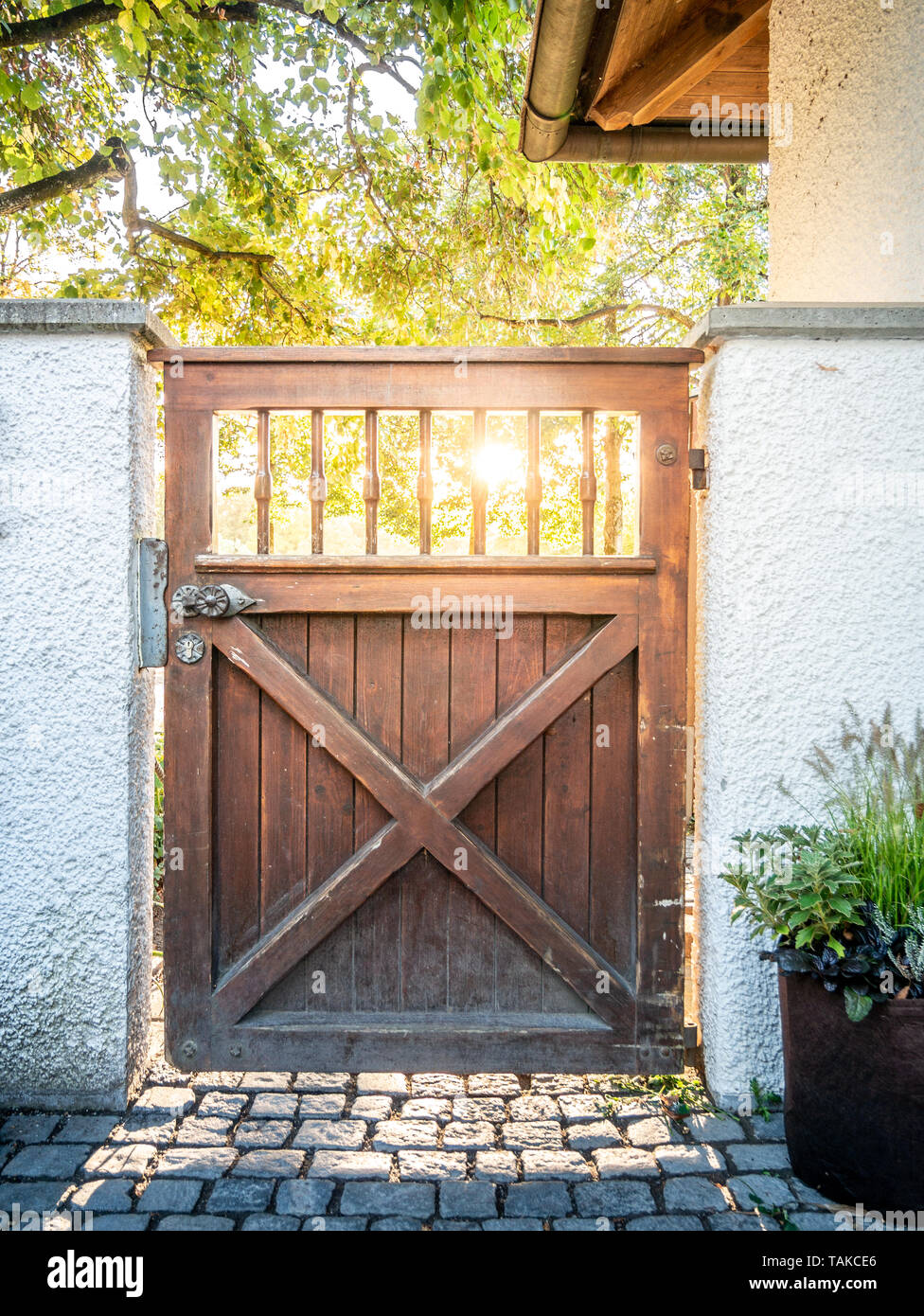 Image of wooden gate with sun rays in the background - Stock Image