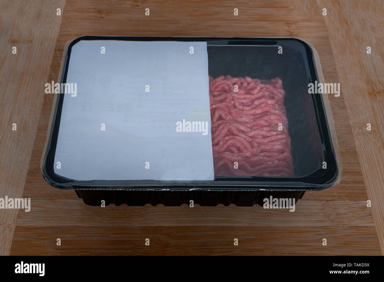 Minced meat in plastic pack with barcode, packed food wooden background - Stock Image