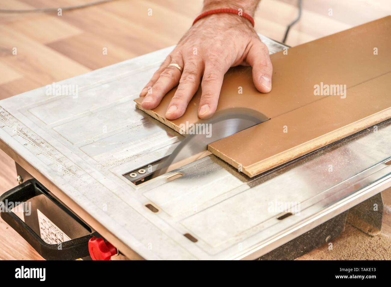Man Cutting Laminate Floor Boards On Circular Saw Detail On Hands