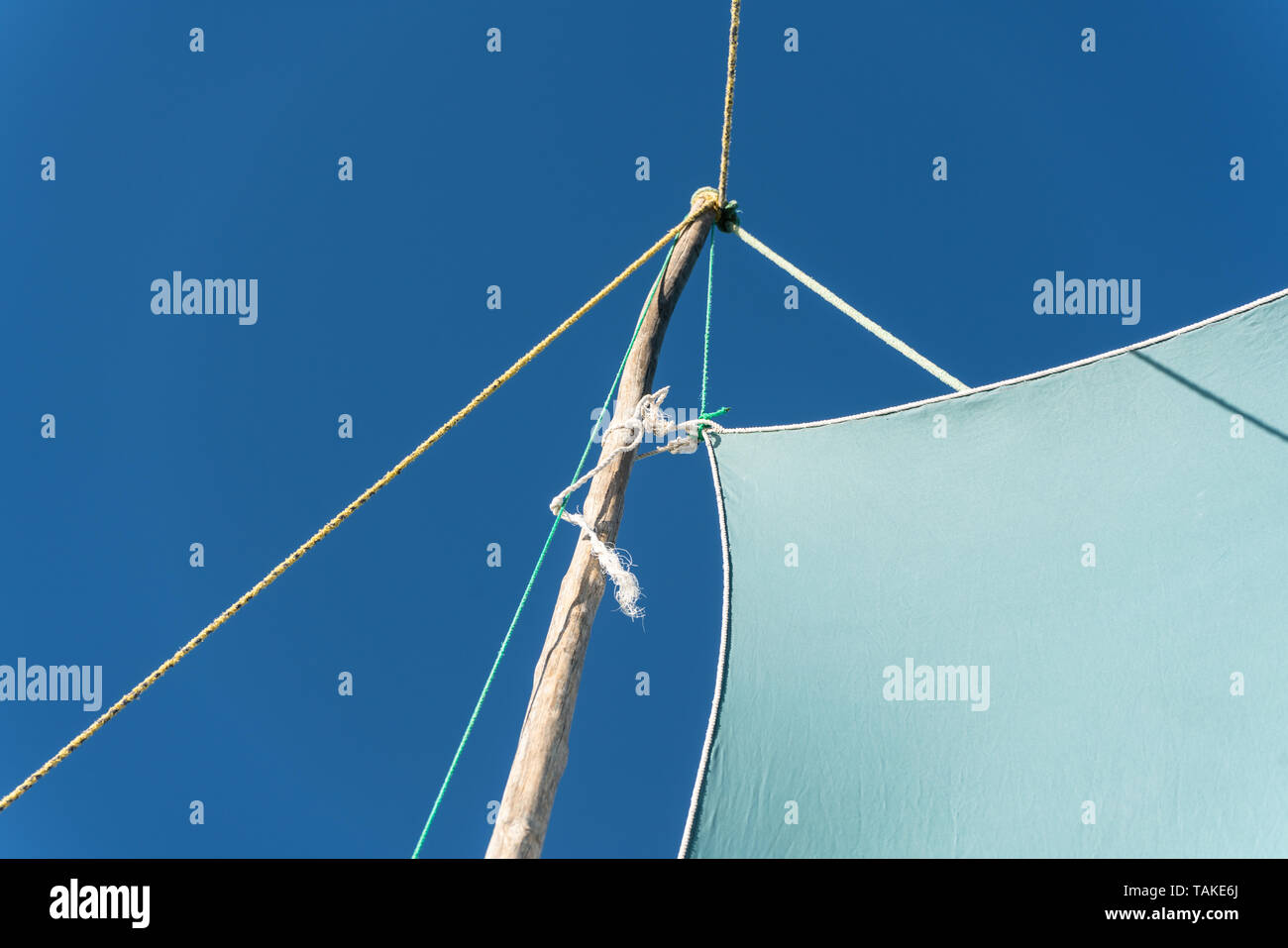 Detail on pirogue - small boat used in Madagascar - mainsail jib blea sky in background - Stock Image