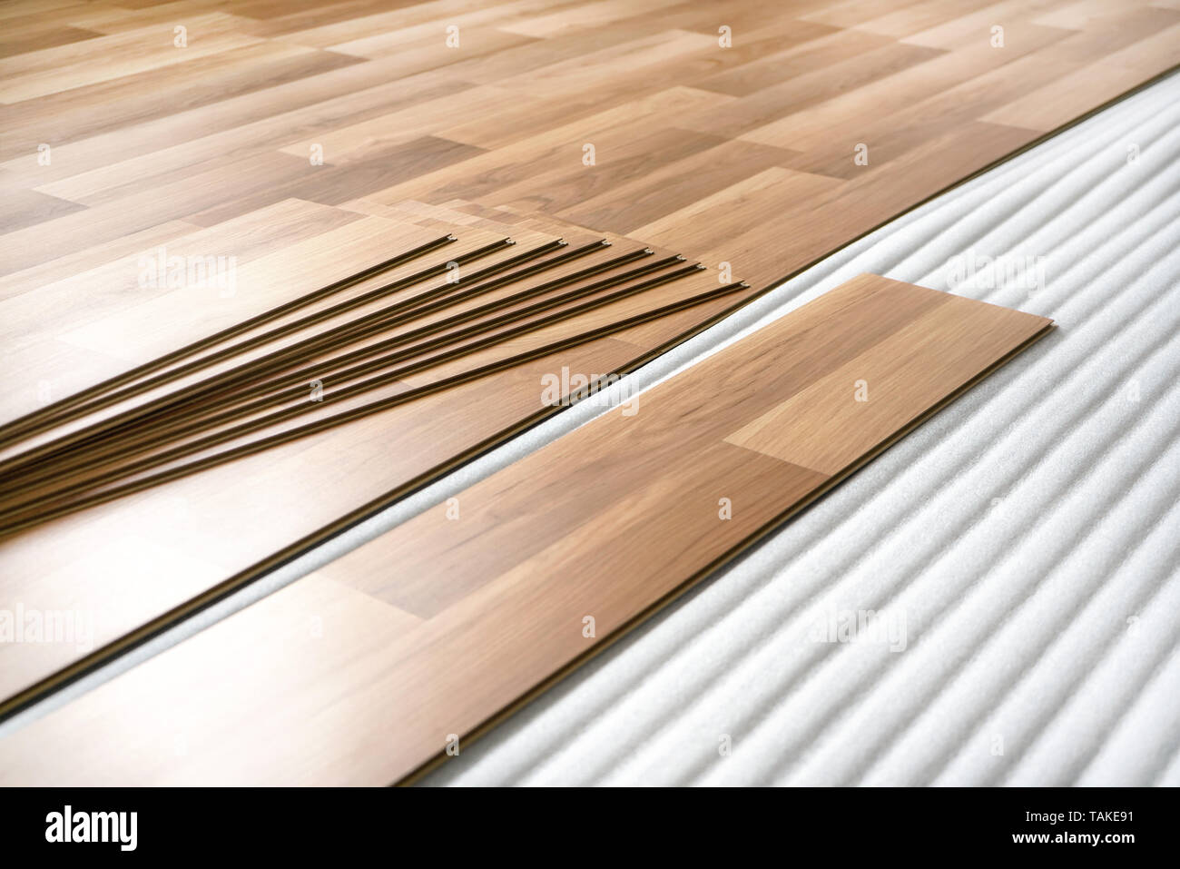 Wooden tiles, ready to be put down as laminated floor on base foam - home flooring renovation. - Stock Image