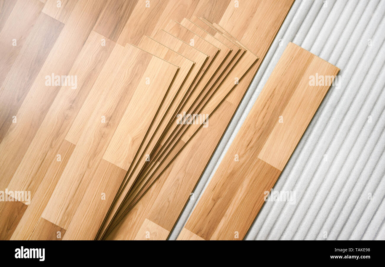 Tiles of laminated floor with wooden effect laying on white base foam, ready to be installed - Stock Image