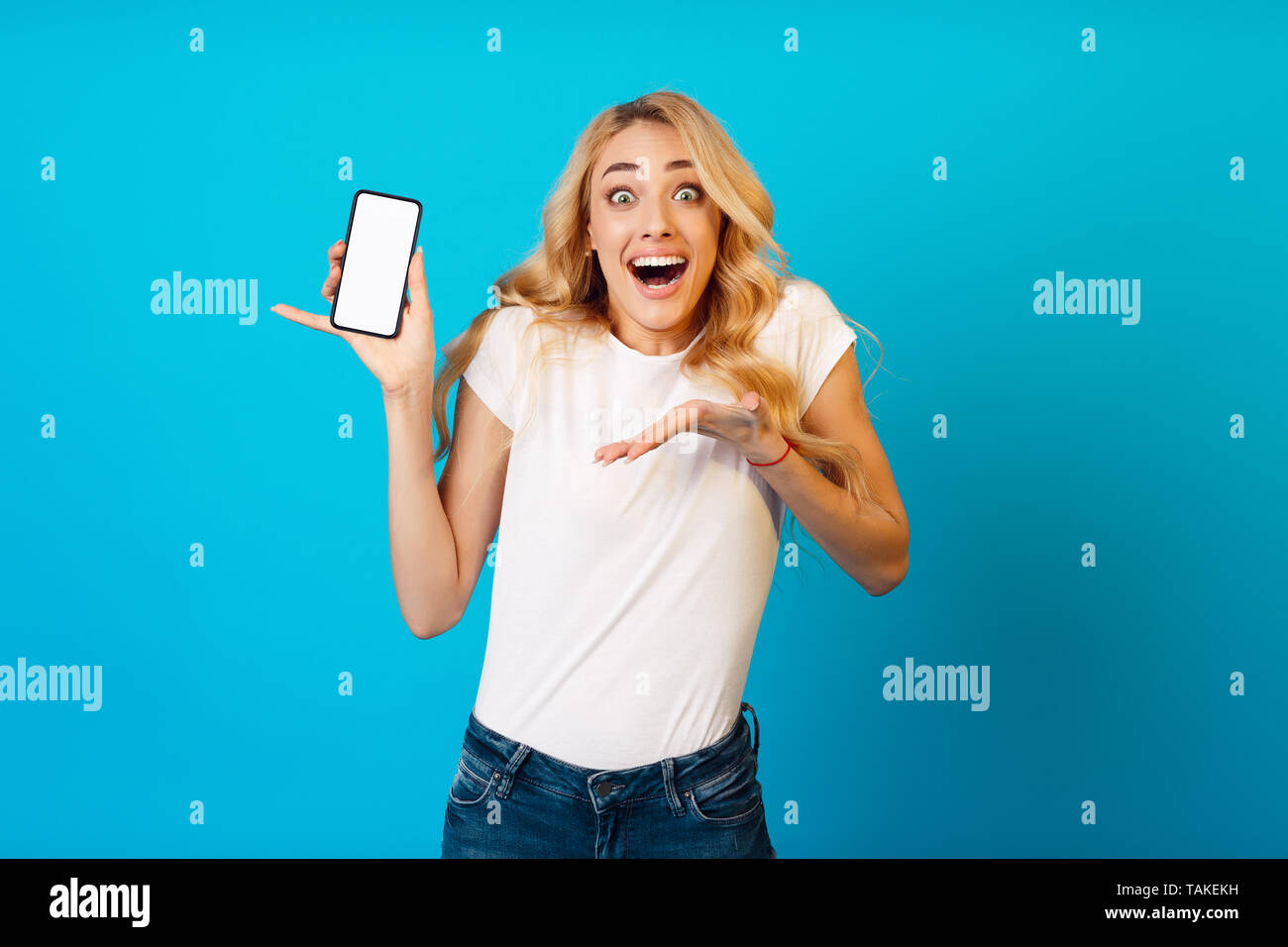 Shocked Girl Showing Blank Smartphone Screen For Advertisement - Stock Image