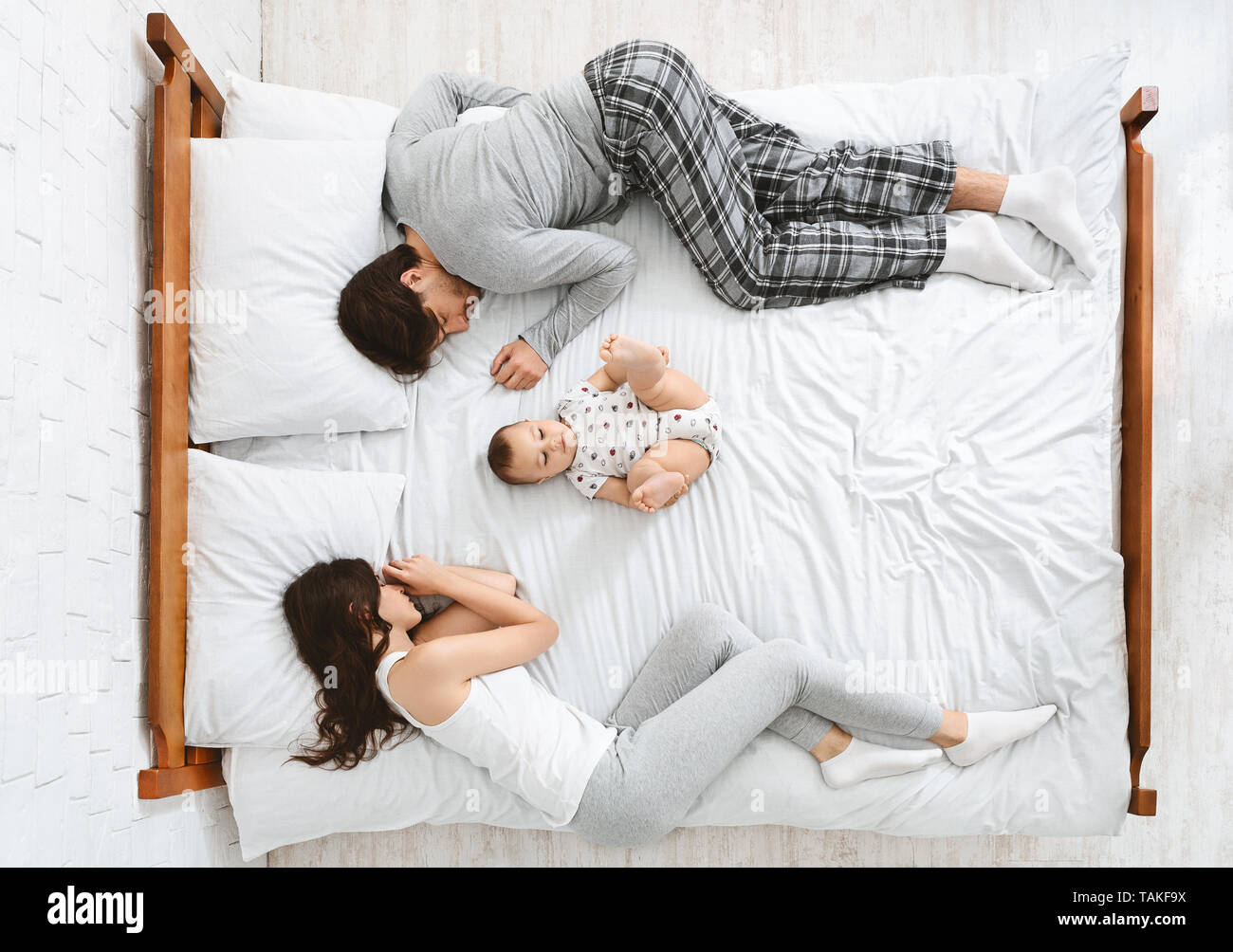 Funny family with one newborn child in the middle of bed Stock Photo