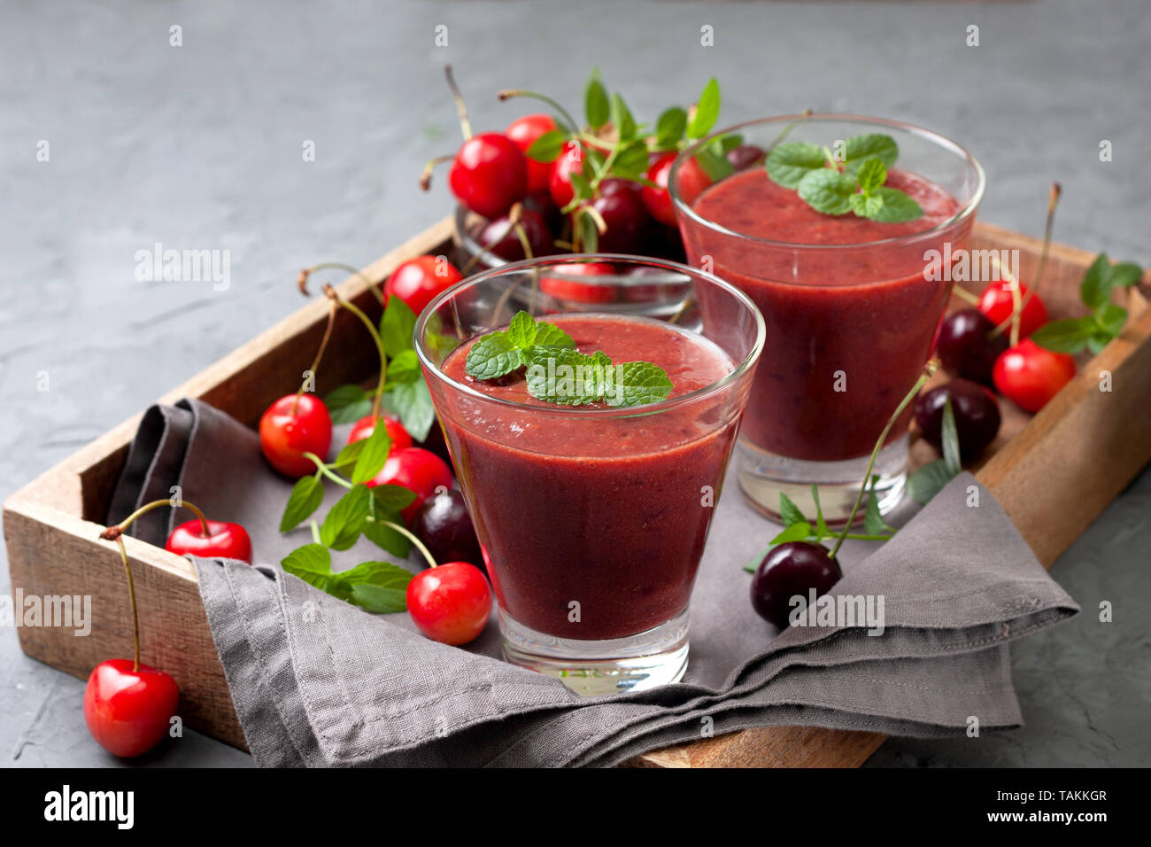 smoothies sweet cherry in a glass, fresh sweet cherry on a gray background Stock Photo