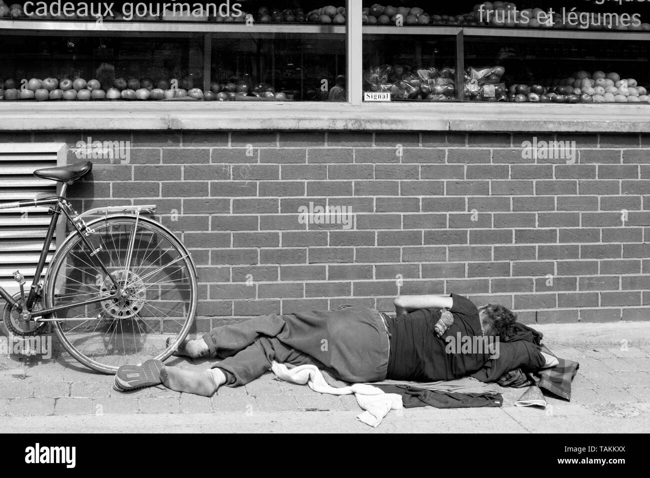 Homeless person sleeping on the floor on a sidewalk , Montreal, canada - Stock Image