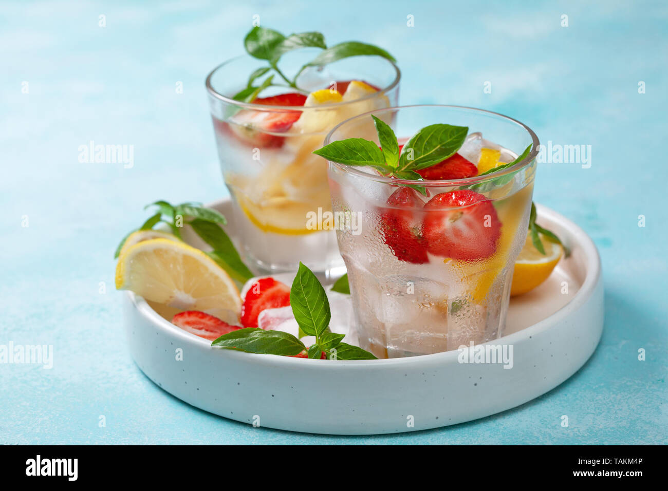 strawberry basil lemonade in a glass, fresh strawberries, basil on a blue background Stock Photo