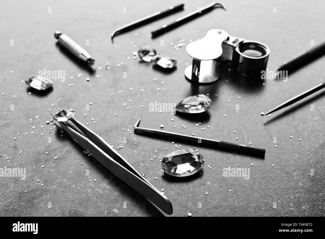 Precious stones and jeweler's tools on grey background - Stock Image