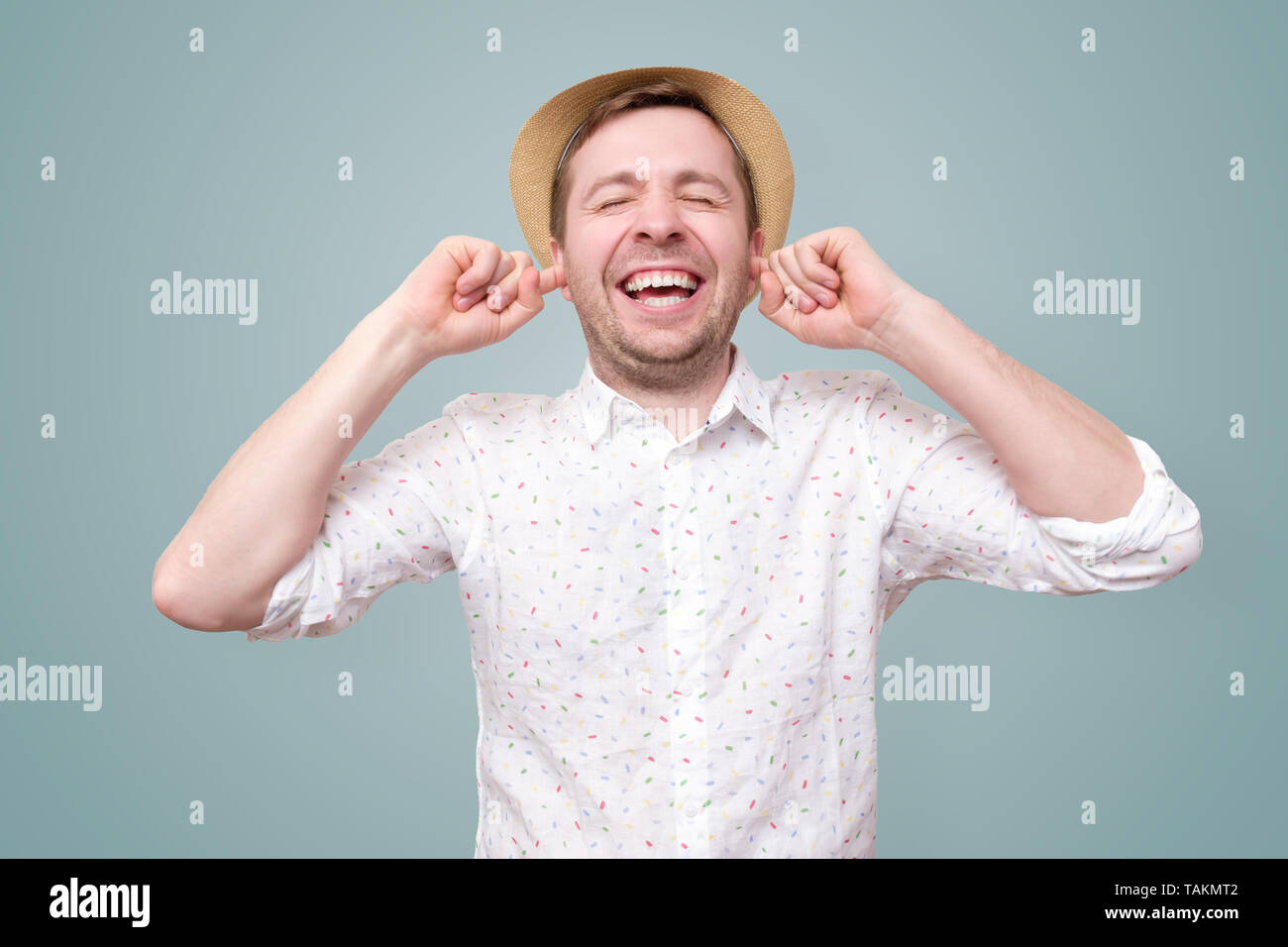 man ears and smiles joyfully as does not want to hear spoiler - Stock Image