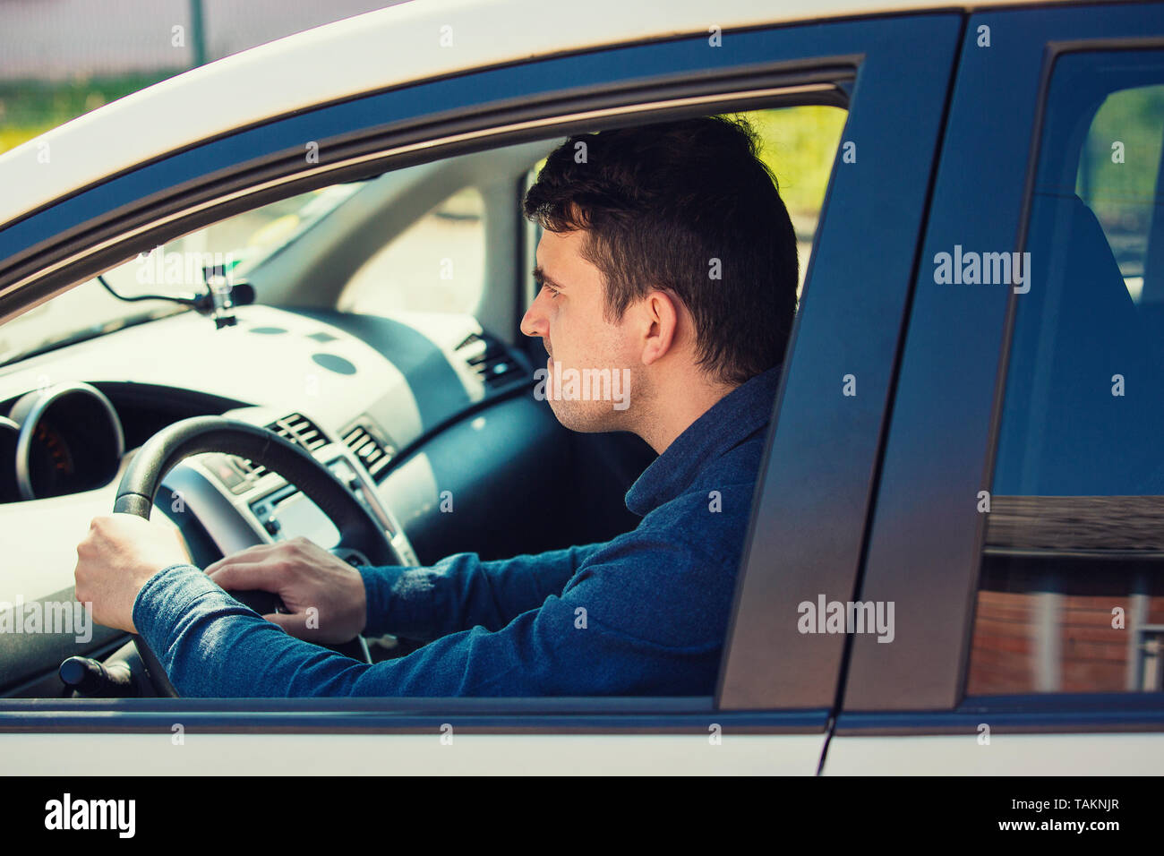 Portrait of furious male driver sitting in the car and honking the car horn angry on the driver ahead. Aggressive guy waiting in the traffic jam, beep - Stock Image