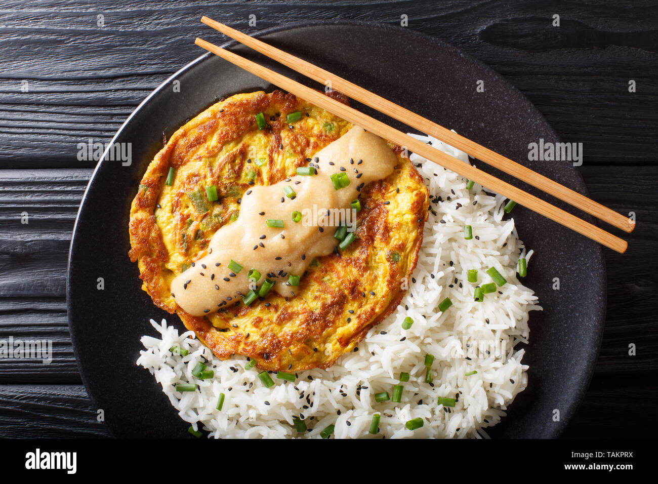 Egg foo yong fried egg patty containing vegetables  and meat with rice garnish close-up on a plate on the table. horizontal top view from above - Stock Image