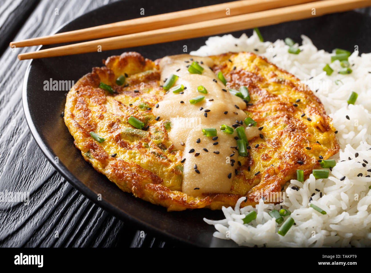 Egg foo yong fried egg patty containing vegetables  and meat with rice garnish close-up on a plate on the table. Horizontal - Stock Image