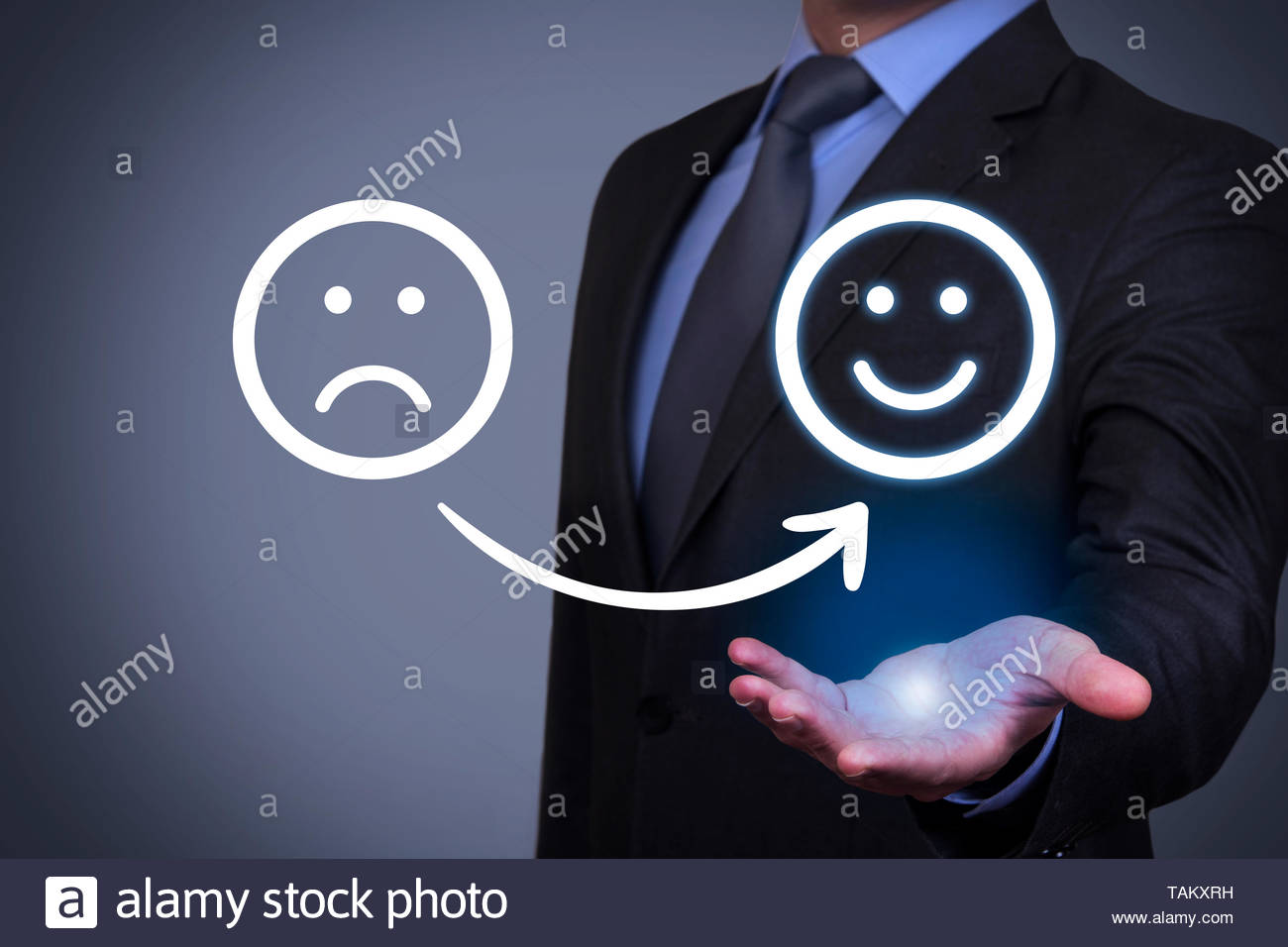 Unhappy and Happy Smileys on Human Hand - Stock Image