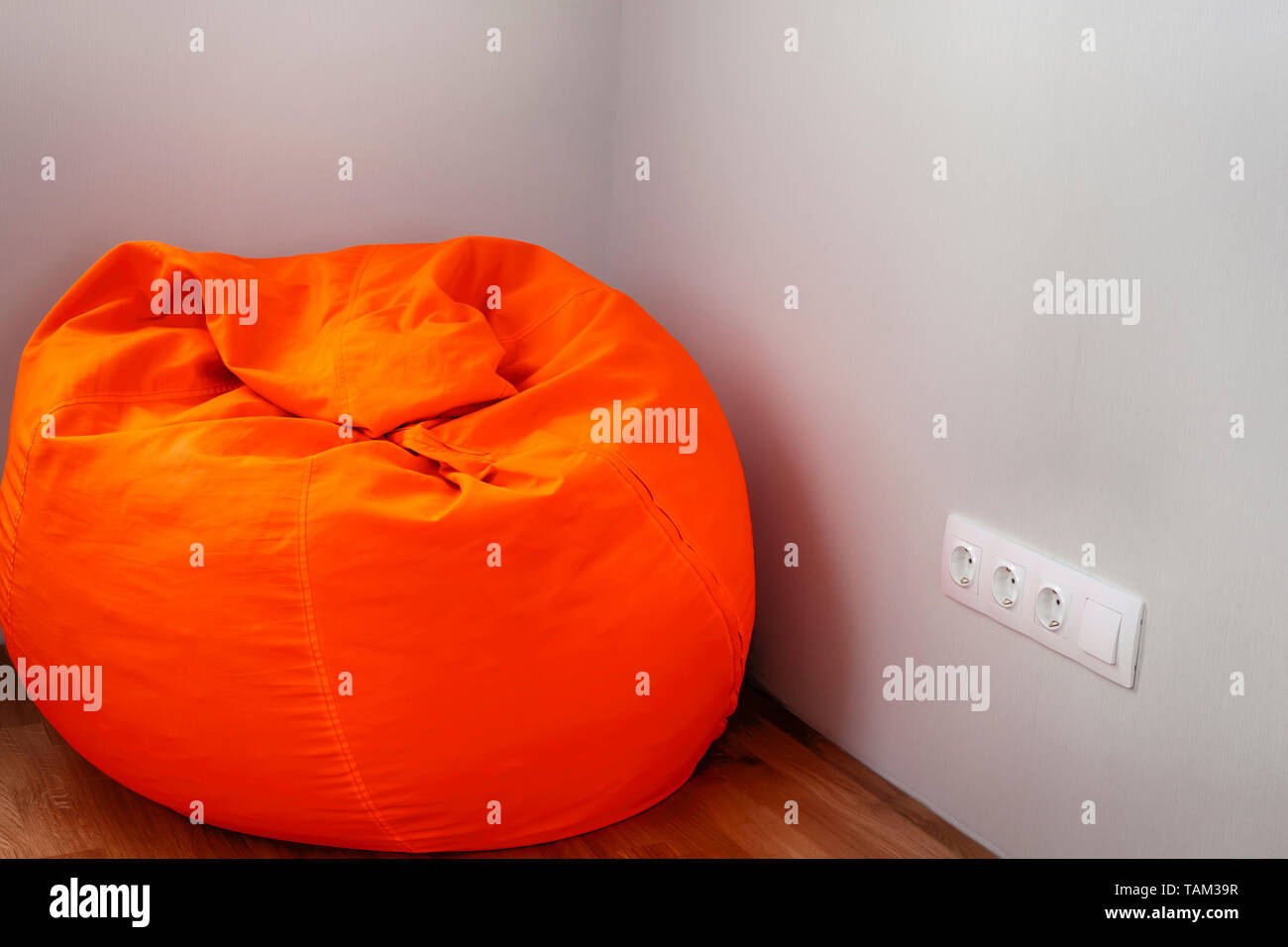 Big orange beanbag in the room corner. - Stock Image