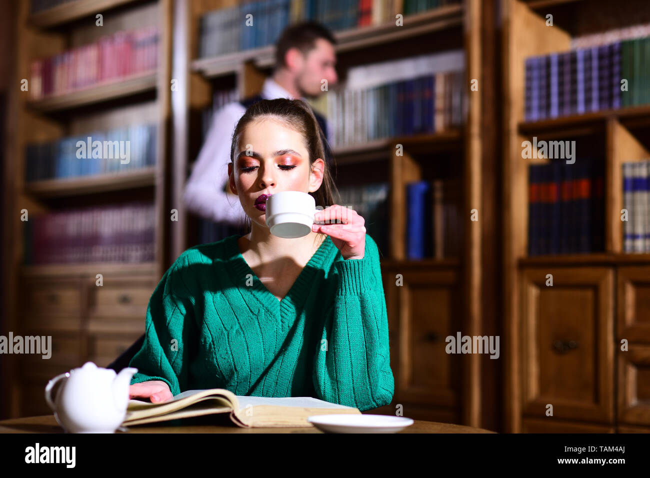 literature cafe with cute girl and man. woman in library read book at teapot drinking coffee from cup. student life in university. agile business and  - Stock Image