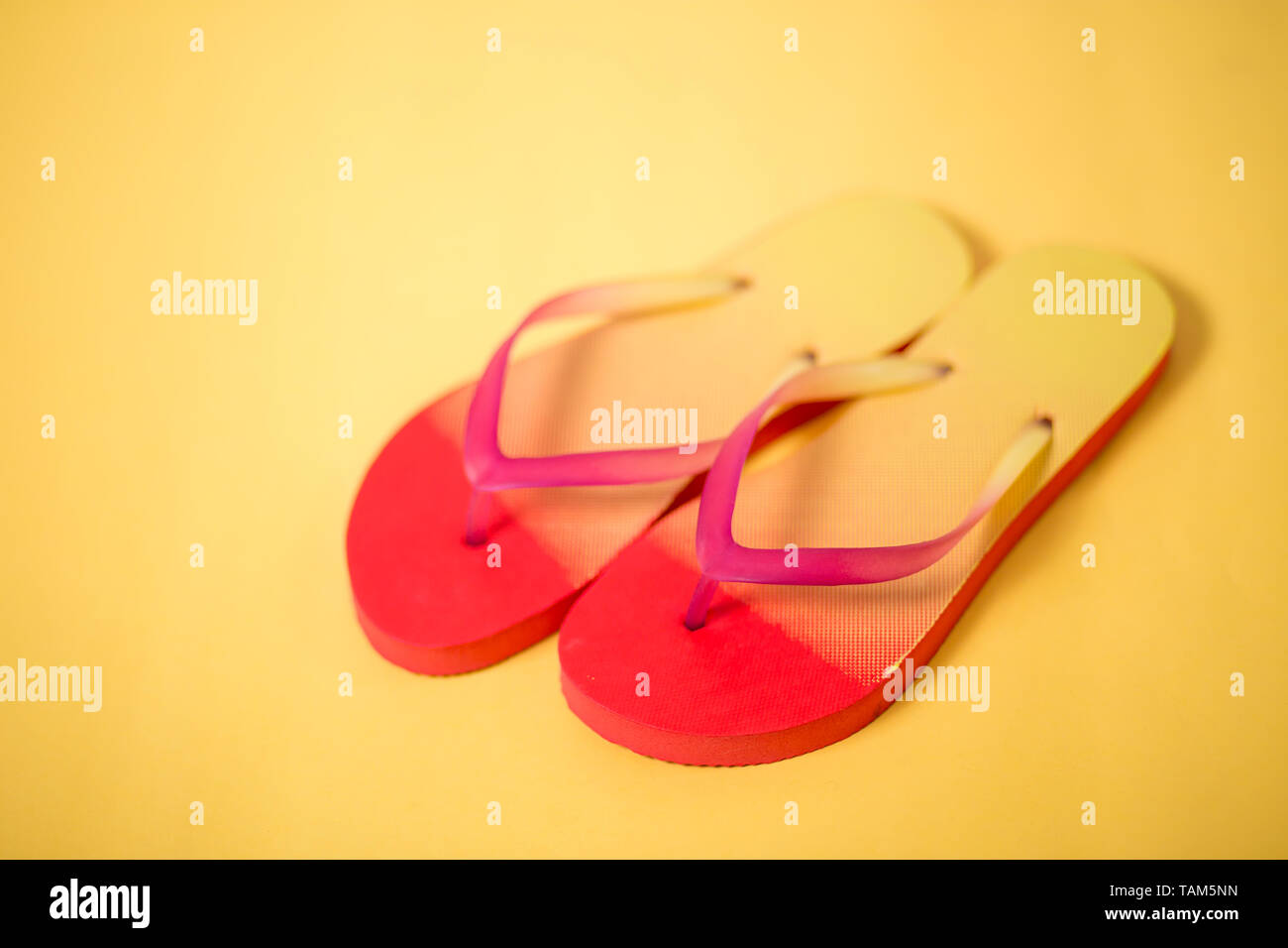 e046b7c4a A studio photo of pink coral yellow sandals. Colorful flip flops isolated  on yellow background