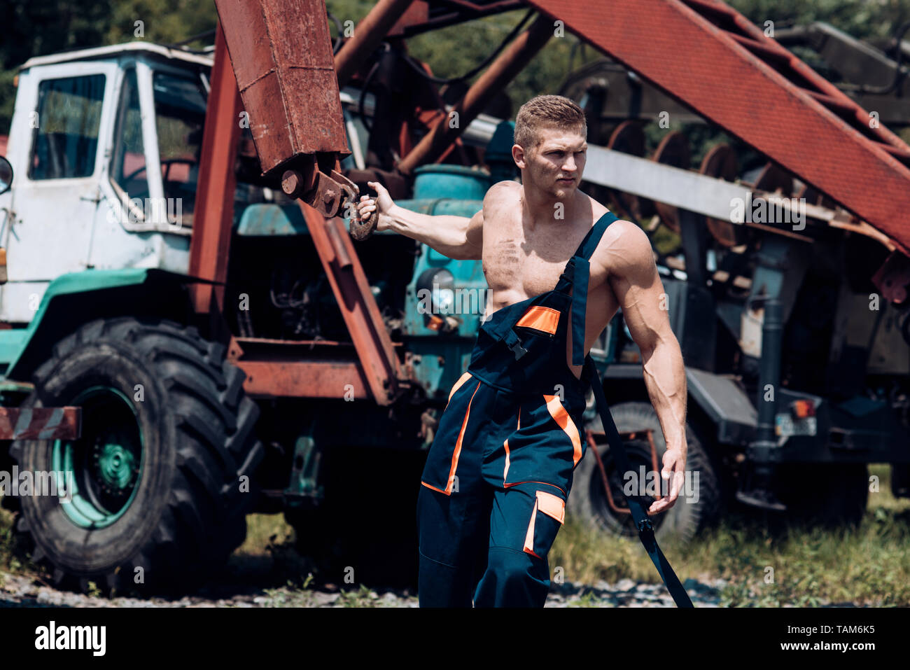 Power concept. Power man pull tractor with crane. Power lifter at construction site. Feel the power - Stock Image