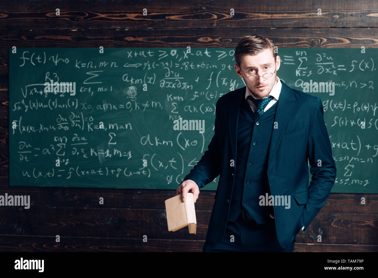 Exacting teacher. Teacher formal wear and glasses looks smart, chalkboard background. Man with high expectations looks unsatisfied with students - Stock Image