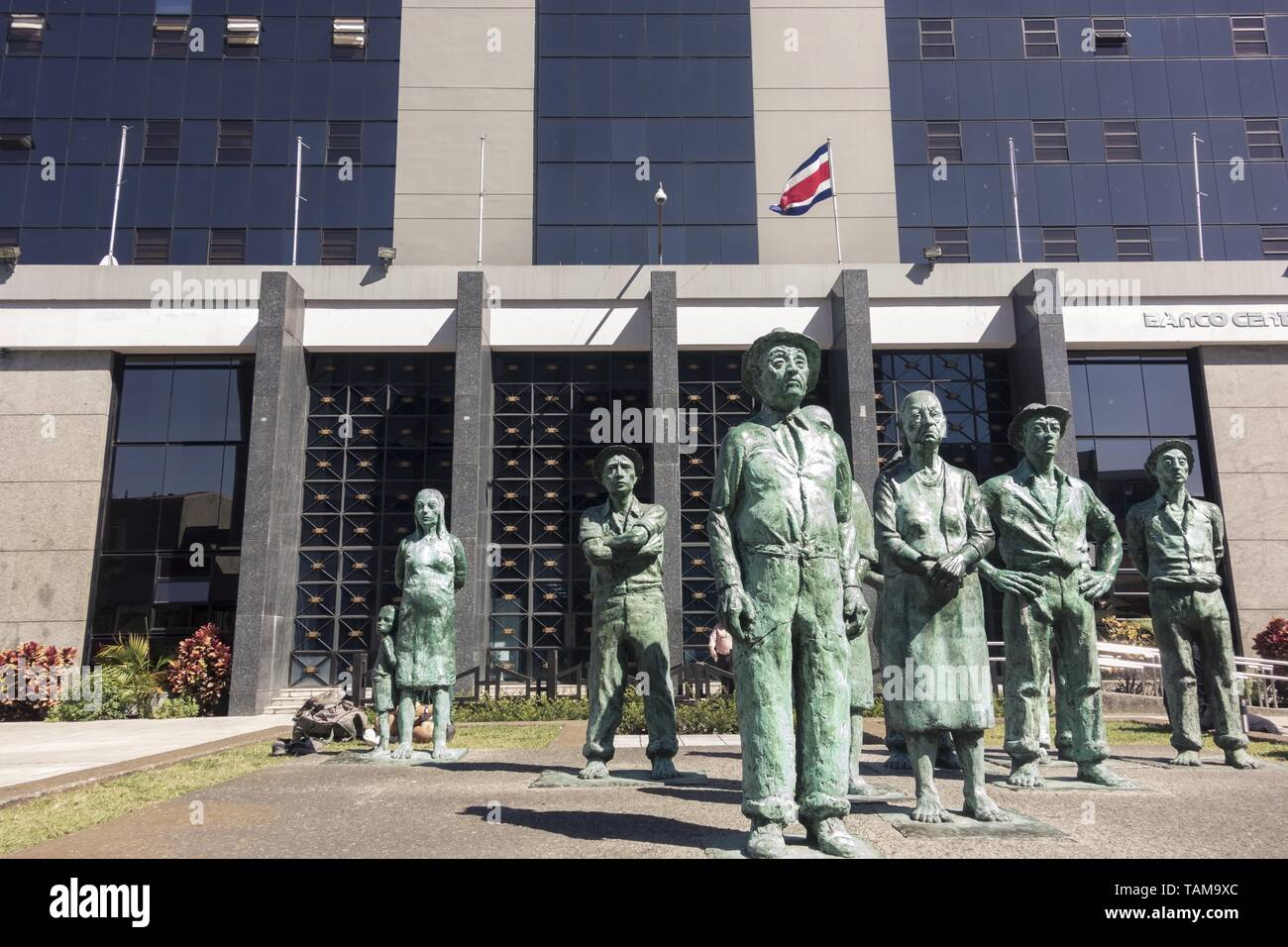 Art Exhibit of Los Presentes Peasant Farmers Sculptures in front of City Center Central Bank Building, San Jose Costa Rica Stock Photo