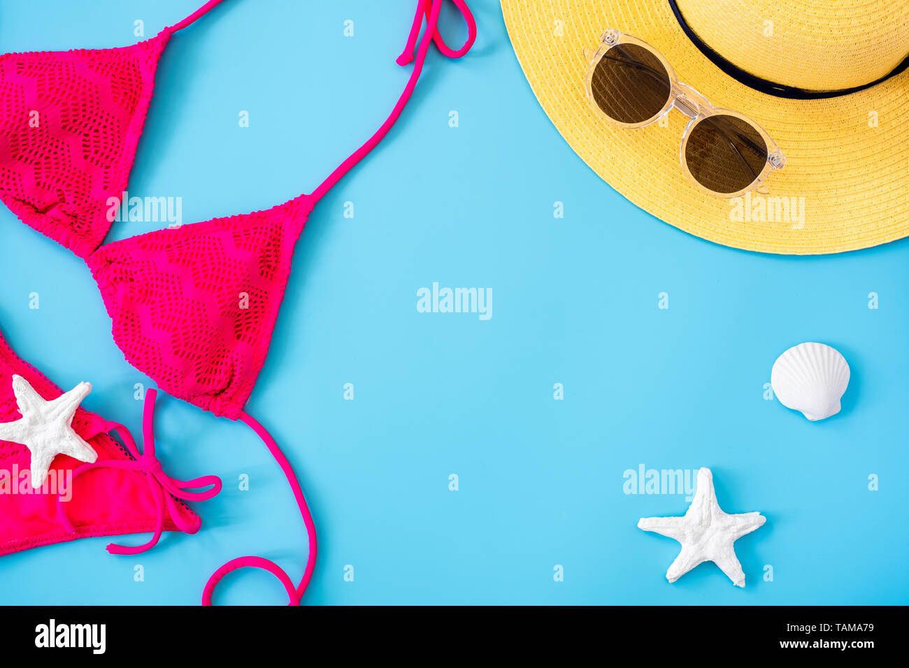 summer blue banner with yellow hat ,pink bikini,sunglasses and seashell on blue background top view. - Stock Image
