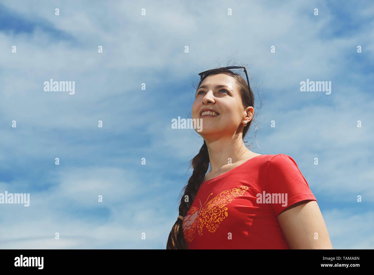 Woman looking up into the blue sky. Portrait of a smiling dreaming girl Stock Photo