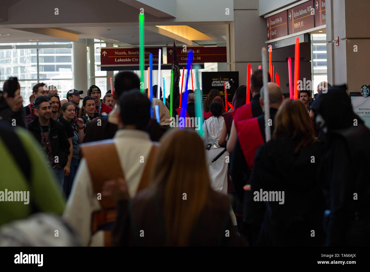 People holding up multicolored lightsabers dressed in cosplay costumes at Star Wars Celebration 2019 - Chicago, IL - Stock Image