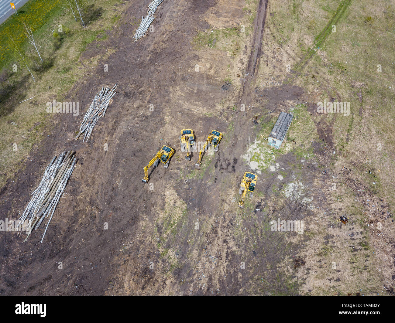 Aerial view of the four yellow crawler excavators that stand on the ground near the construction site and await the start of the working day digging t - Stock Image