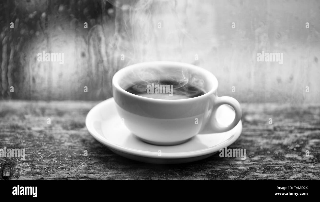 Wet glass window and cup of hot coffee. Autumn cloudy weather better with caffeine drink. Enjoying coffee on rainy day. Coffee time on rainy day. Fresh brewed coffee in white cup or mug on windowsill. - Stock Image