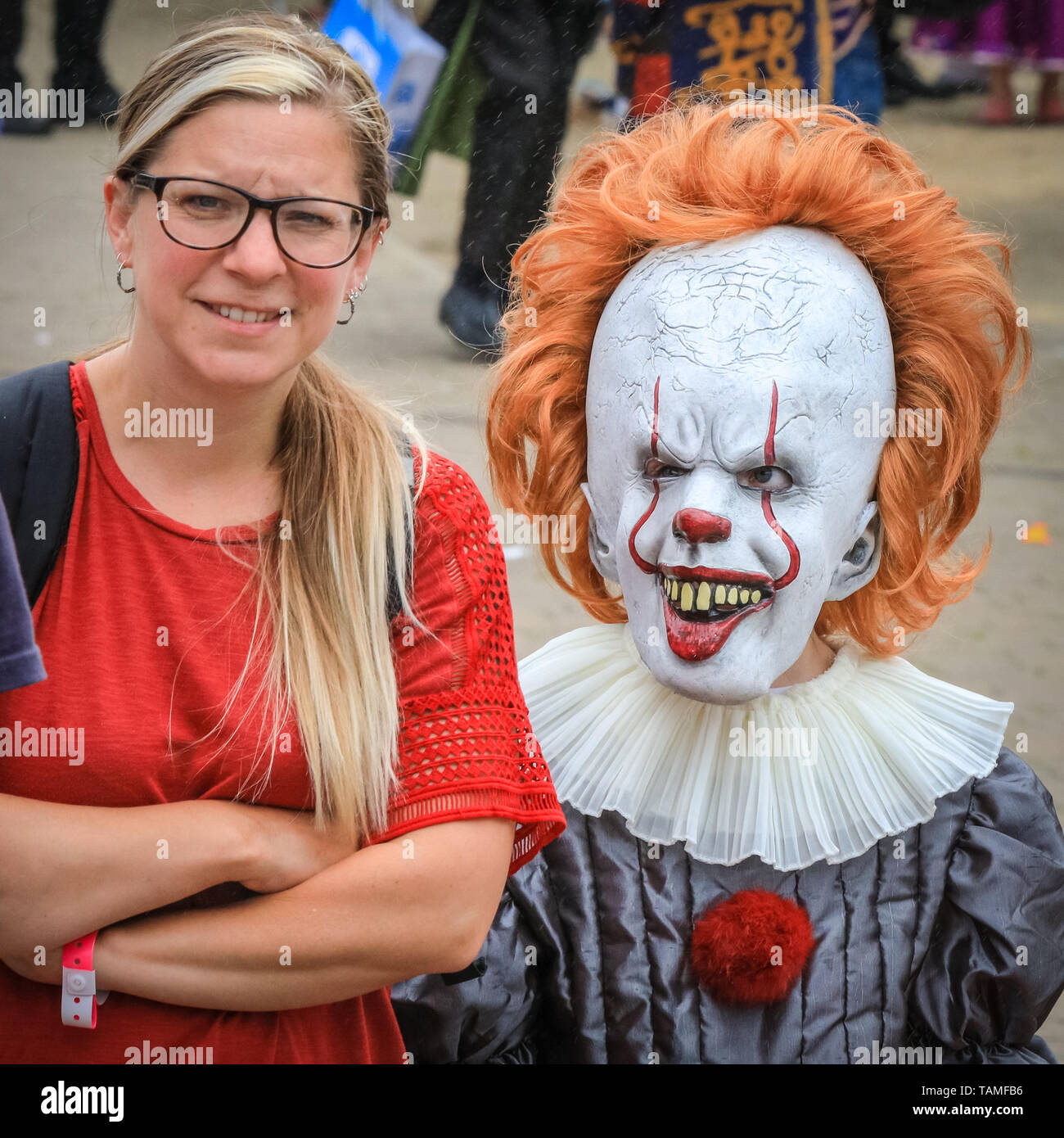 London, UK. 26th May, 2019. A mum looks bemused that her young daughter has decided to come as horror character 'Pennywise' from 'IT' MCM Comicon's third and final day once again sees thousands of cosplayers and fans of comics, games and sci fi and fantasy turn up in fantastic costumes and outfits at ExCel London to celebrate their favourite characters. Credit: Imageplotter/Alamy Live News - Stock Image