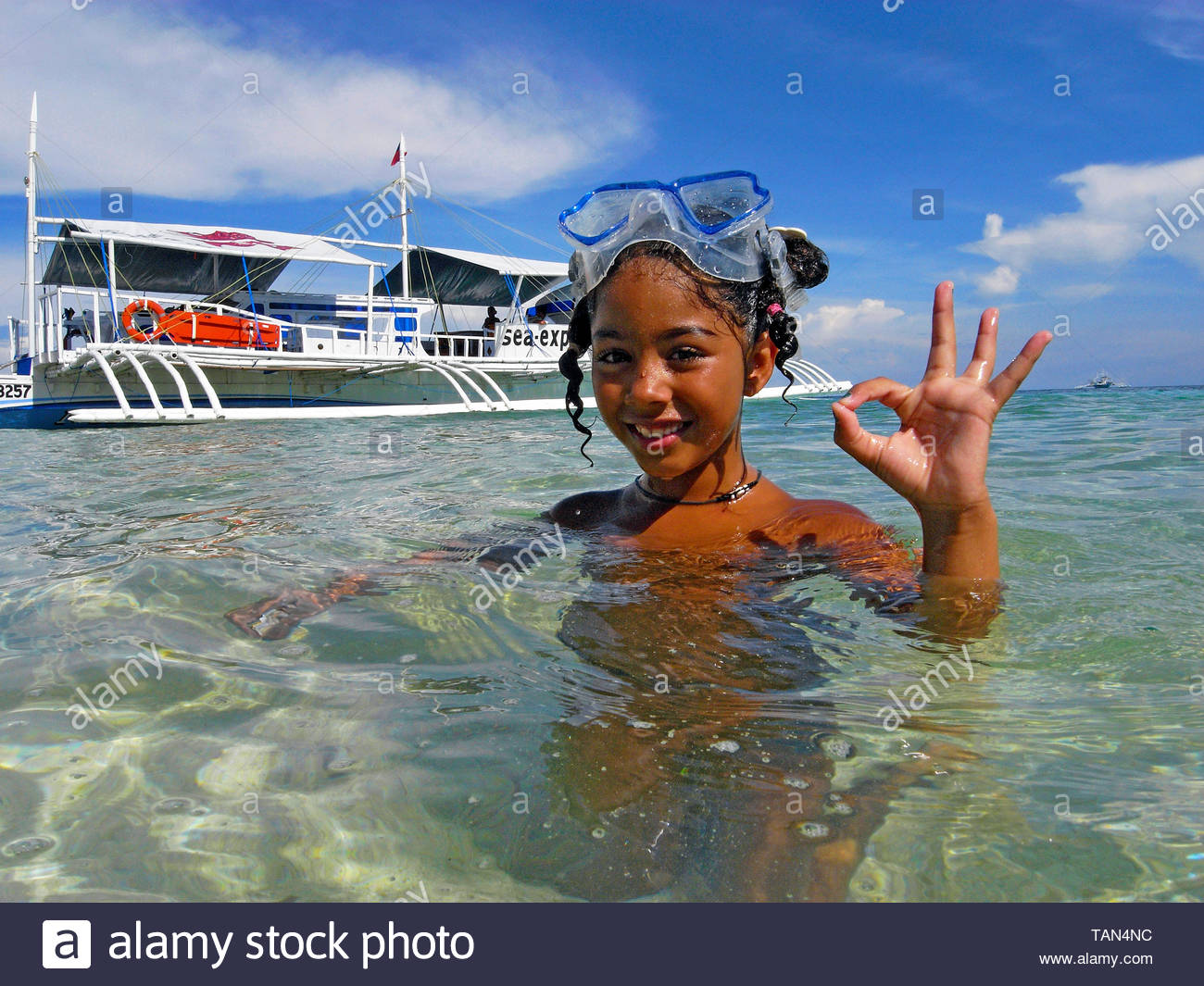 Little philippine girl with diving mask shows the o.k. sign, lagoon of Malapascua island, Cebu, Visayas, Philippines - Stock Image
