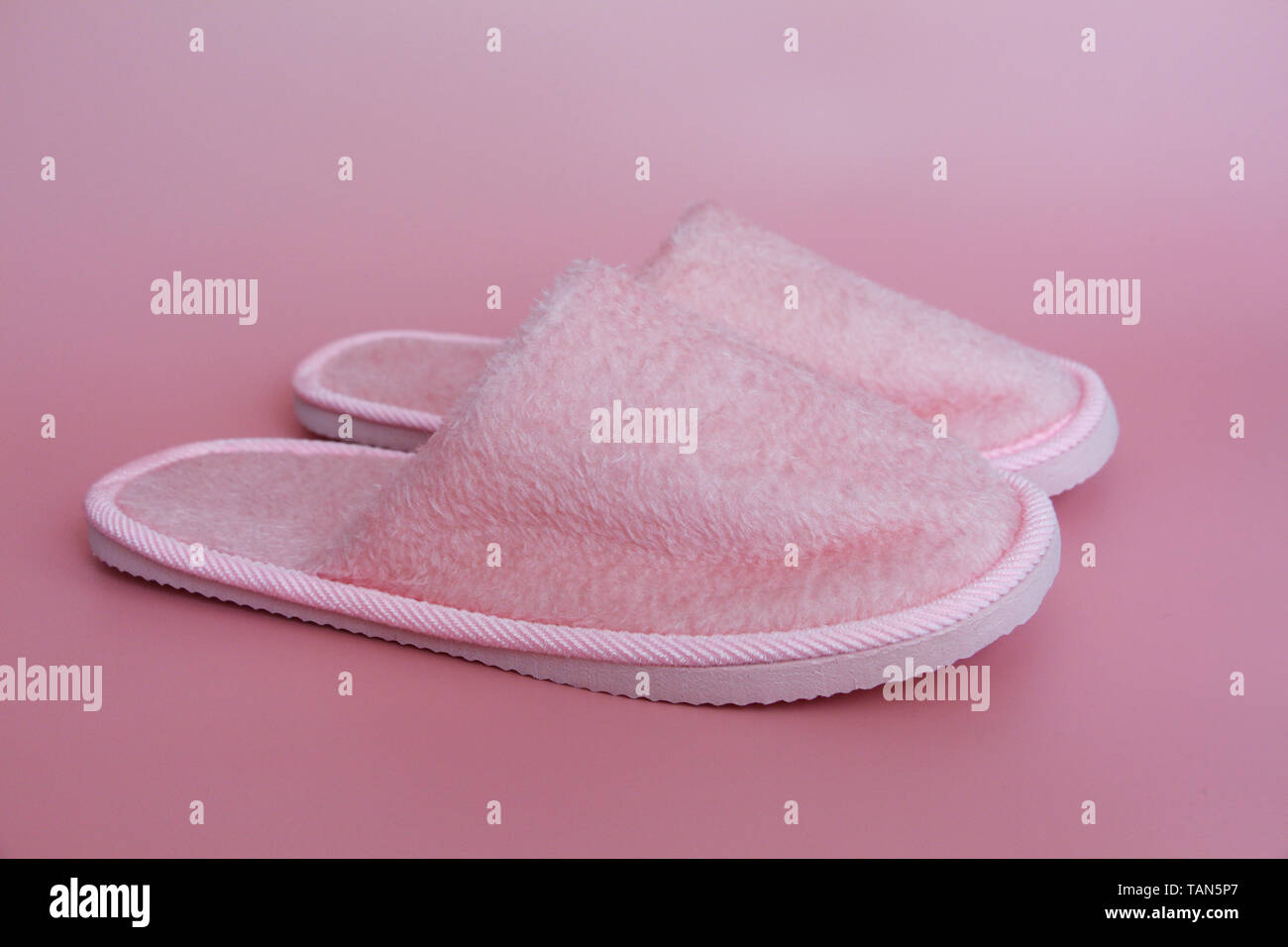 Pink slippers on a pink background. A pair of household terry slippers. Nothing more. - Stock Image