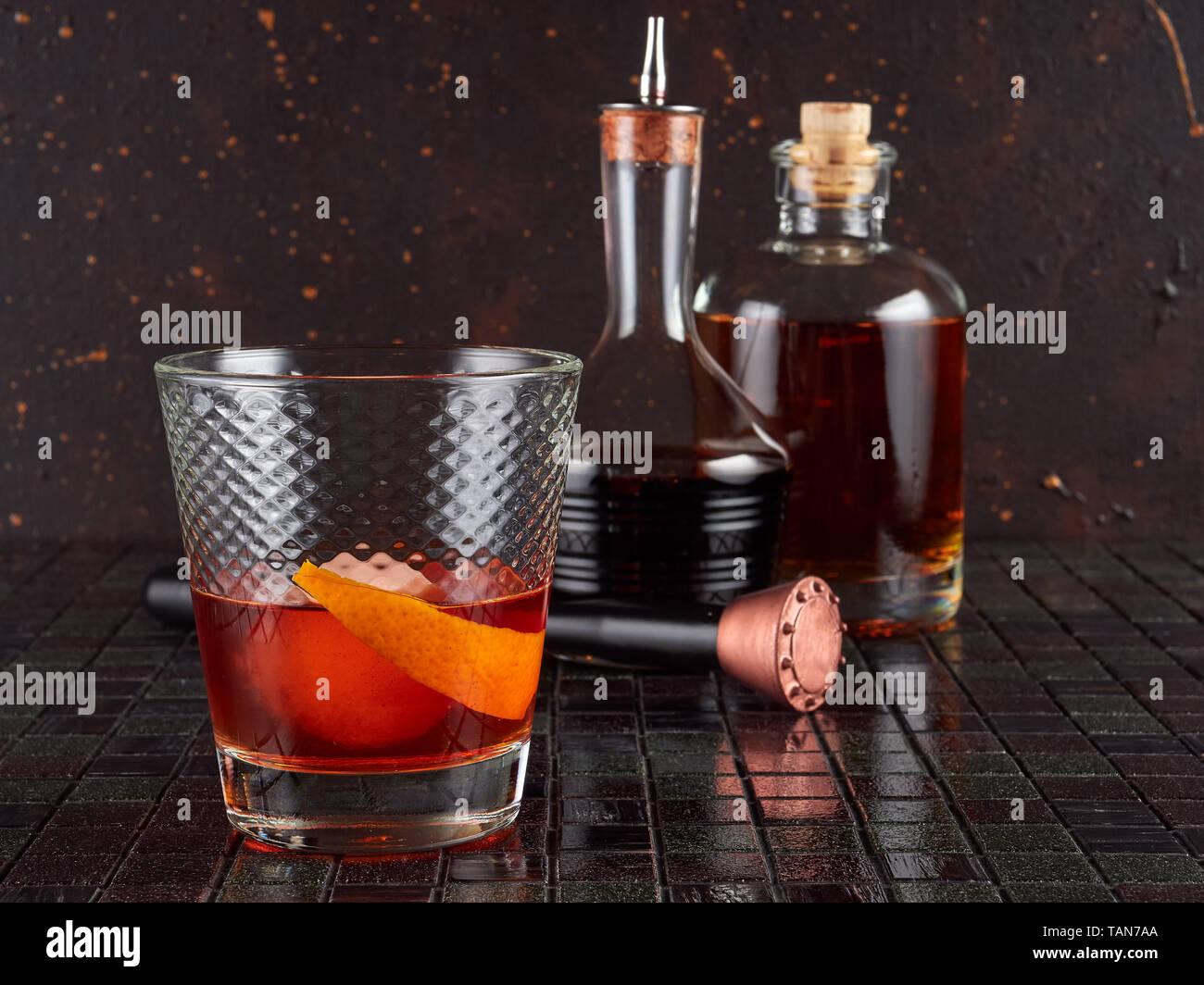 Old fashioned: a cocktail made by muddling sugar with bitters, then adding bourbon, and a twist of citrus rind - Stock Image