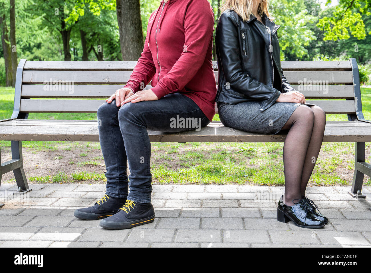 Relationship and body language concept. Couple - man and women sitting on the bench - Stock Image