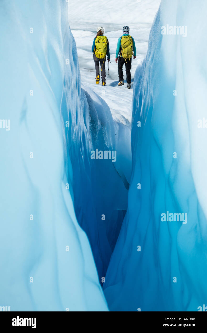 Two ice climbers walking away from a narrow crevasse. The women are ice climbing guides on the Matanuska Glacier in Alaska. - Stock Image